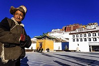 Old Tibetan man with fur hat standing in front of Potala palace in Lhasa, Tibet, China.
