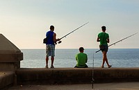 People fishing along the Malecón seawall in Central Havana, Cuba.