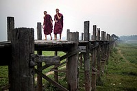 Two Buddhist monks walk along the U Bein bridge at sunrise, Amarapura, Myanmar.