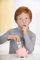 Little boy with red hair, hesitating before putting a 20 euros banknote into the slot of his pink piggy bank