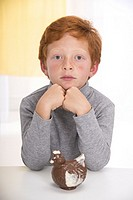 Little boy with red hair, elbows on the table, head resting on his hands, thoughtful in front of an easter chocolate hen