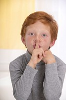 Little boy with red hair, his elbows on a table, one finger in front of his mouth, to say ´ hush ´ and make silence