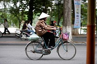 Woman cycling in Hanoi, North Vietnam.