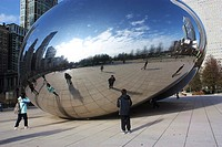 Tourists looking at their reflections in the Chicago Bean in Millennium Park in Chicago, IL, USA.