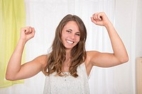 Young woman lifting hers arms to express her happiness