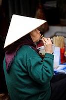 Woman wearing a traditional Non La Hat, Old Quarter, Hanoi, Vietnam
