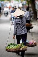 Woman carrying a traditional Vietnamese 'don ganh' yoke, Old Quarter, Hanoi, Vietnam