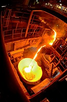 Hot steel pouring in ladle car train in steel plant.
