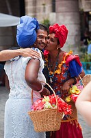 Women in traditional clothing giving a kiss to a tourist in the old Havana-Havana Vieja district, Havana, La Habana, Cuba, West Indies, Central Americ...