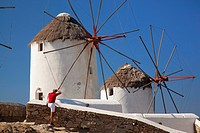 Tourist taking the photos of the traditional windmills, Mykonos, Cyclades Islands, Greek Islands, Greece, Europe