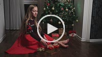 Happy woman putting presents under Christmas tree