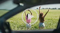 View through car window of women jumping in field