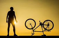 A mountain biker on sea wall watching the sun rise over the North sea at Seaton Carew on the north east coast of England, United Kingdom. Europe,.