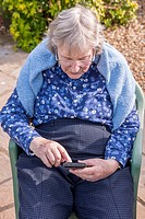 A woman in her 80´s using a smart phone in the Uk.
