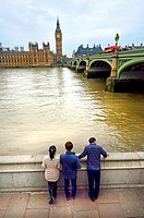 London, England, UK. Asian tourists looking across the River Thames to the Houses of Parliament.