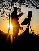 Silhouetted by an evening sunset, a scenic painter works at his easel under an evergreen tree in in Laguna Niguel, CA.
