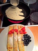 Homemade Bavarian pancakes with strawberries, sugar powder and fresh blueberries