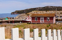 An old dilapidated shed and a fishing vessel. Brigus, Newfoundland, Canada.