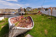 A old dilapidated fishing vessel with homes in the background. Brigus, Newfoundland, Canada.