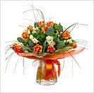Bouquet of narcissus, tulips and other flowers in glass vase isolated on white background. Closeup.