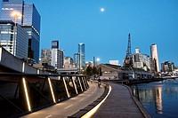 Cyclists on Jim Stynes Bridge, with Melbourne skyline.