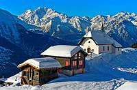 Snow-covered chapel Kapelle Maria zum Schnee against the peaks of the Pennine Alps, Bettmeralp, Valais, Switzerland.