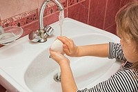 Five-year girl soaps hands with soap in the sink.