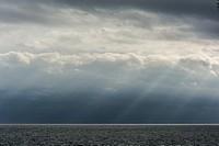 The sky seems to cry tears of light, divine scenery on the coast of Barcelona.