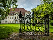 An old solitary wrought-iron locked gate in front of an abandoned baroque manor house in Mecklenburg-Pomerania, Germany, standing in a park environmen...