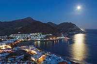 The seaside town of San Jose in the nature reserve Cabo de Gata-Nijar. With full moon at dusk. Almeria province, Andalusia, Spain.