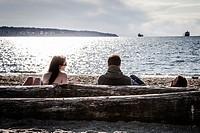 Couple sitting near the sea on sunset.