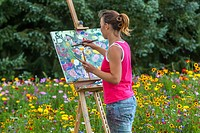 The woman painter with her stand in the open air painting blossomed flower beds.