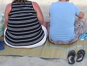 Couple from behind sitting on mat