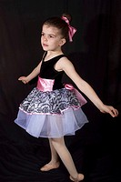 Little girl in her dancing outfits pose and have fun afront of the camera.