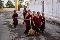 Young novice Buddhist monks sweeping around the grounds of the Shwe Yan Pyay Monastery in Nyaungshwe, Myanmar.