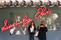 Woman posing in front of Elvis neon sign at Graceland, Memphis, Tennessee, USA.
