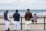 Asian men and boy looking out to sea at Redcar, north east England, United Kingdom.