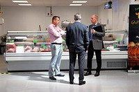 Three men chatting in front of Butchery section of a food wholesaler.