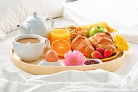 Breakfast tray in bed in hotel room.