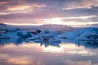 Iceland, Jokulsarlon Glacier Lagoon, icebergs and ice chunk at sunset.