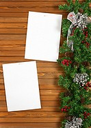 Garland with Christmas ornaments, pine cones and sheets of paper on wooden background.