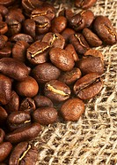 Roasted coffee beans on burlap background. Macro shot with tilt effect.