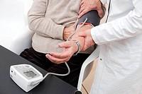 Doctor checks blood pressure of senior female patient.