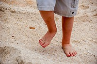 Partial view of a little boy´s bare feet running on sand.
