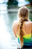 Back view of a 20 year old blond woman with bare shoulders with her hair in a pony tail in an outdoor setting in the summer