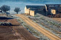 Dirt road and dilapidated farmhouse. Almansa. Albacete province. Spain
