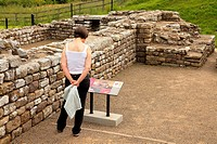 Woman reading information sign. Chesters Roman Fort and Museum bathhouse. Chollerford, Hexham, Northumberland, England, United Kingdom, Europe.