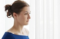 Indoor fashion portrait of pretty young beautiful sensual stunning woman dark red hairs in blue sweater posing on background of window curtains.