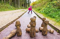 Young girl plays at skittles on a forest playground.