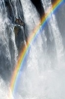 Rainbow amongst the mist, spray and cascading water of Victoria Falls, Africa.